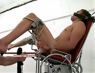 Tied to a gyno chair, stripped nude, interfered with, mouth gagged with ripped underwear and fastened with a thick leather belt, cock and balls roped up, dildo hammered into cunt with a mallet, flogge...